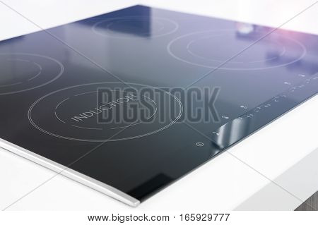 Modern black induction cooker on white countertop