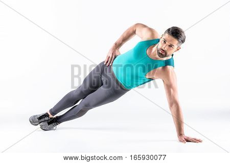 Muscular man doing side plank exercise and looking at camera