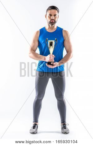Young muscular man in sportswear holding trophy and looking at camera