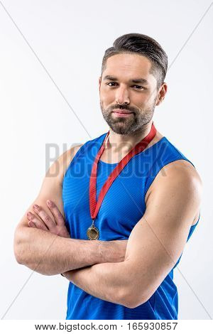 Young man in sportswear with gold medal award looking at camera on white
