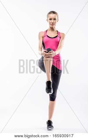 Young woman in sportswear stretching her legs and looking at the camera on white