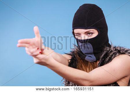 Woman in black balaclava making gun gesture. Crime and violence on blue studio shot