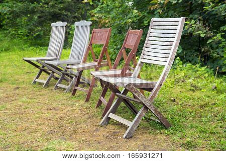 Set of old wooden chairs of different design in a garden