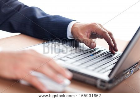 Closeup of a Businessman Typing on a Laptop Keyboard