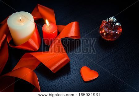 Burning candles, wrapped in red ribbon. With a heart and a bottle of perfume. Gift for Valentine's Day. Dark texture with a romantic symbol of love by fourteen february.