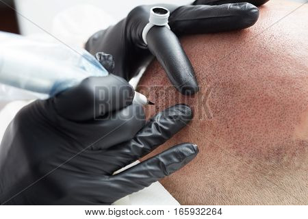 Cosmetologist making permanent makeup on male head - tricopigmentation