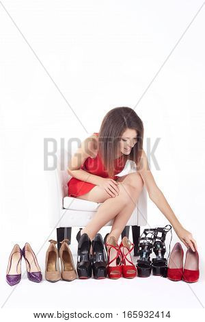 woman sitting on chair and trying on high heeled shoes