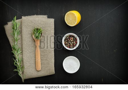 Rosemary with wooden spoon lying on the linen napkin with spices on black wooden background. Copy-space composition