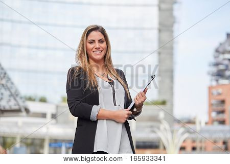 smiling businesswoman in front of office building
