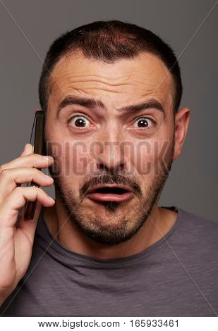 funny foolish man talking to mobile phone