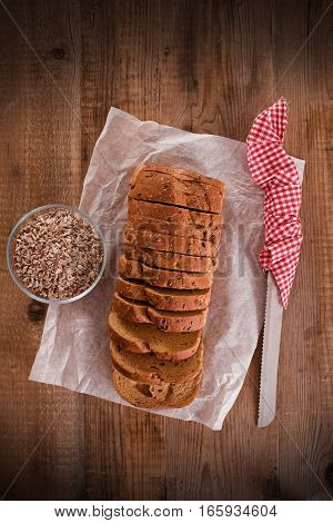 Whole wheat bread with seeds on wooden table.
