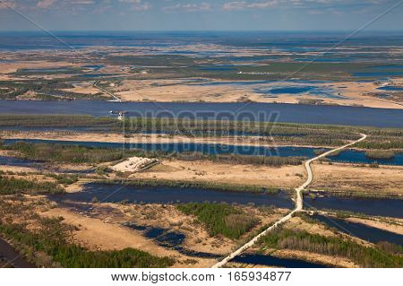 Road to the ferry boat at the bank of river during spring in West Siberia top view. Great plain is divided into many parts by a lot of number of rivers and channels. Water meadows are covered by yellow last year's grass.