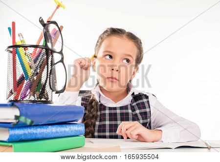 Schoolgirl doing homework and thinking about her task on white