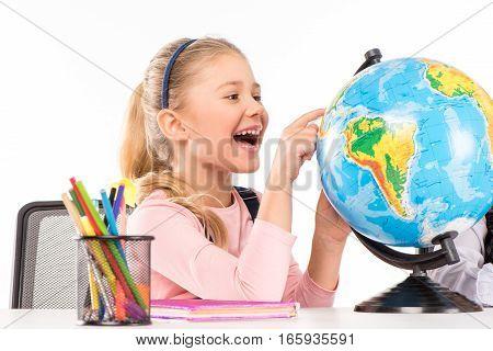 Happy schoolgirl exploring globe during homework isolated on white