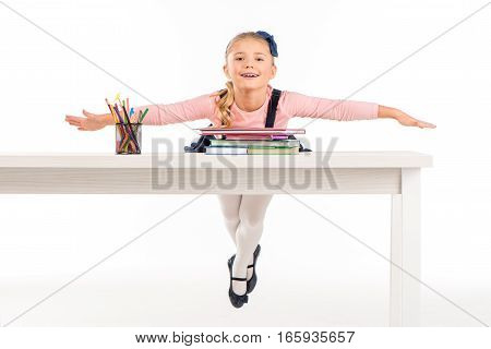 Cheerful schoolgirl lying on desk with books on white
