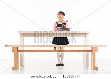 Serious schoolgirl standing at desk and looking on books on white