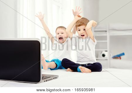 Two joyful boys, sitting in front of a laptop screen in the children's room