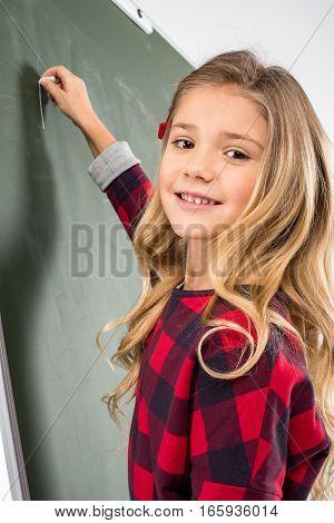 Smiling schoolgirl writing with chalk on blackboard