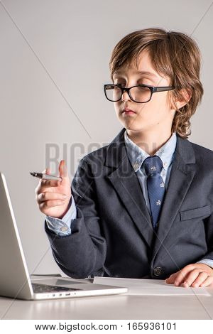 Schoolchild in business suit sitting on desk with pen in hands looking at laptop