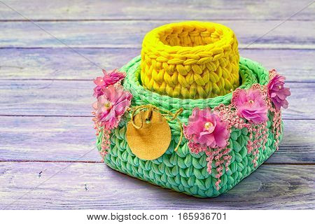 Knitted Baskets Decorated With Lace Flowers, With A Blank Circular Paper Label. Copy Space On A Wood