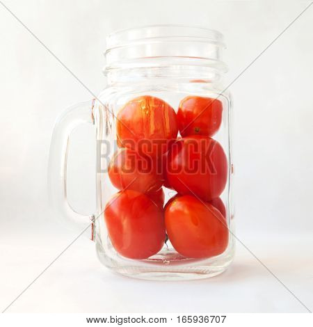 Tomato juice drink smoothie in a glass concept. Plum tomatoes in a transparent jar mug isolated on white. Many small fresh red vegetables in a cup