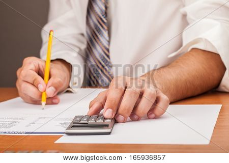 Close-up of a Businessman Analyzing Financial Figures with Calculator
