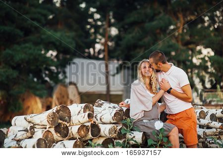 Pregnant couple in love against the backdrop of a beautiful sunset in nature