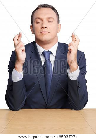 Portrait of a Businessman with Eyes Closed and Fingers Crossed