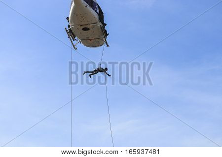 Soldier rappelling from helicopter in blue sky