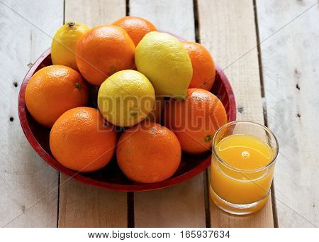 sweet and rip oranges and lemons on a red plate on a wooden table with orange juice in glass