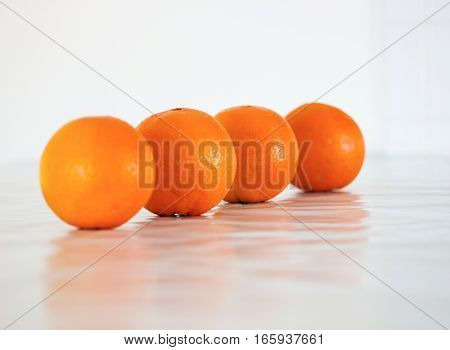 four sweet rip oranges on a white background