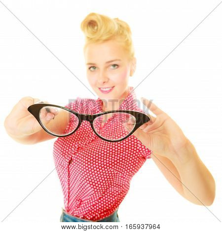 Ophthalmology sight problems stylish eyeglasses concept. Blonde pin up girl wearing red shirt holding black retro glasses behind face. Studio shot isolated