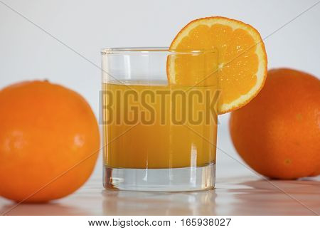 fresh orange juice in glass with the slice of orange and two oranges