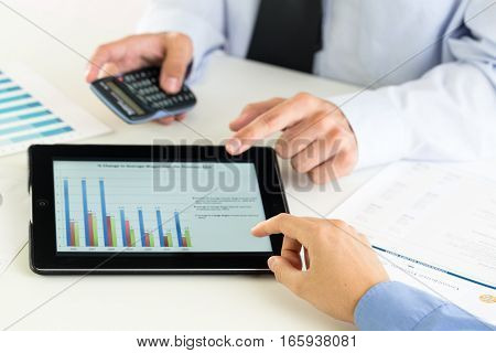 Close-up of a Businessmen Analyzing Business Graphs on a Digital Tablet and Paper