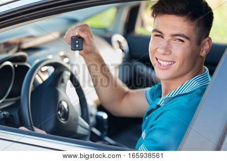 Portrait of Young Man Showing Car Key in his Car