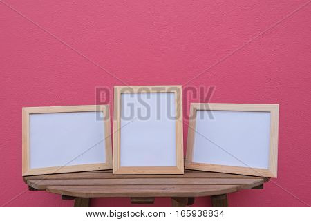 Three photo Frame on a wooden on pink background .