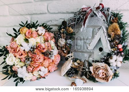 Beautiful details of wedding bouquet located in new year interior with white background. Bouquet have roses in rose and white colors.