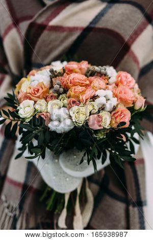 Beautiful wedding bouquet of roses white and other colors in the hands of the bride is wearing a glove