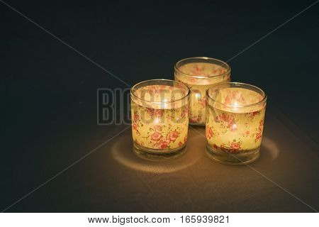 Three tea lights with burning candles in the dark