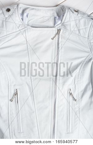 White leather jacket on white background. Leather jacket macro details. Jacket zippers and pockets
