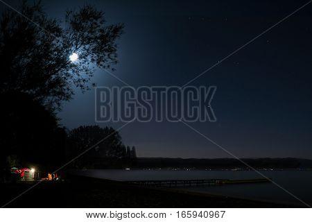 Night camping by the lake, at full moon
