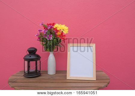 photo Frame on a wooden and Flowers in jar and Lantern on pink background .