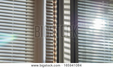 The sun shining through the blinds and are reflected in the window