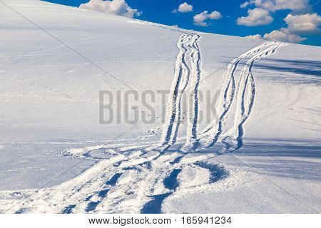 Two snowy track on the mountainside leaving afar. Winter countryside views in the background of the cloudy blue sky
