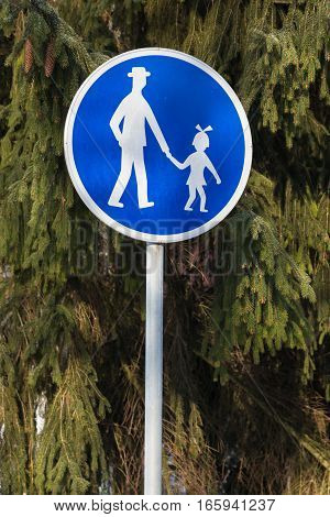 Traffic sign - pedestrian path: an adult and a girl holding hands on a background of green fir trees. Road sign used in Slovakia