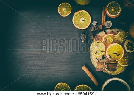 Tea in a mug with dried citrus fruit and spices on a black wooden surface empty space top view vintage toning