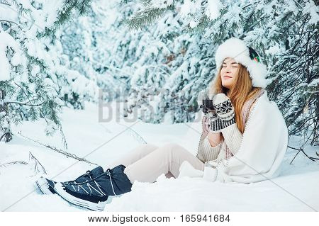 Beautiful woman is drinking tea on the background of a winter fairy-tale forest