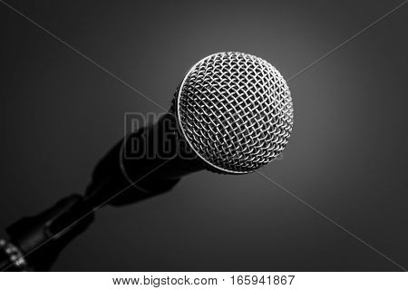 Microphone with metal body in holder isolated on black background close-up