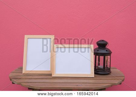 photo Frame on a wooden and Lantern on pink background .