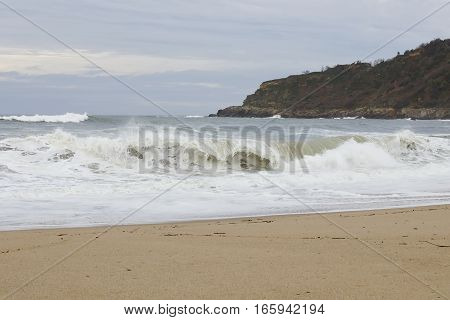 View of a beach with a big wave crashing at the shore.